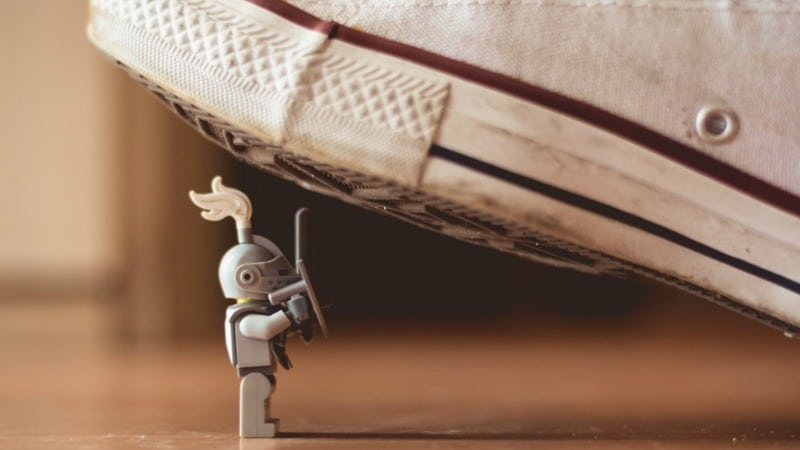 Lego figure with too much debt about to be crushed by a giant shoe.