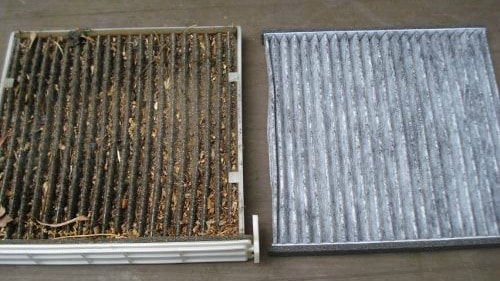 A filthy cabin air filter next to a brand new one