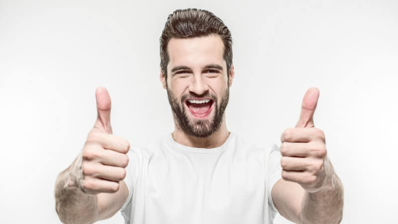 A happy man giving thumbs up and demonstrating how to not suck at life.